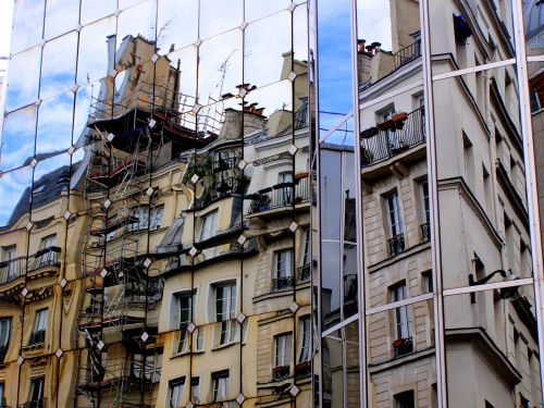 Offices clad in mirrored panels reflect copies of the homes opposite. Walking in Rambuteau, Paris, where each new building, clad in mirrored panels, appears to be a distorted, reverse copy of the old building opposite. This is one of three photos taken one minute apart