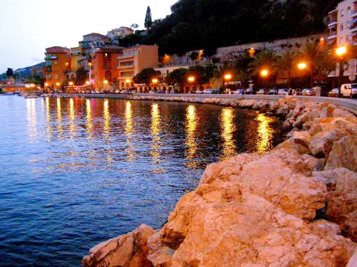 On The Rocks at Villefranche-Sur-Mer. An idyllic location. Not only was the orange light from the lamps reflecting wonderful beams across the water, it was casting an orange glow onto the rocks before me. https://witness.theguardian.com/assignment/552e3c5be4b0dfcbad6c3d9f/1477352