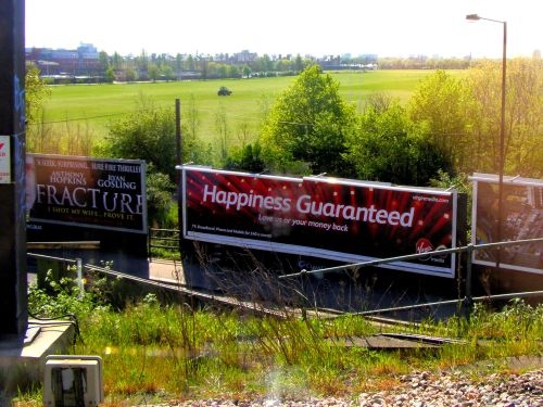 """West Brompton, London """"Fracture – Happiness Guaranteed"""" My train stopped outside West Brompton station, overlooking Wormwood Scrubs Park. I couldn't help but smile at what almost seemed to be either an appropriate advert for A&E or a dark message. https://witness.theguardian.com/assignment/54f71d23e4b041160571f72b/1513315"""