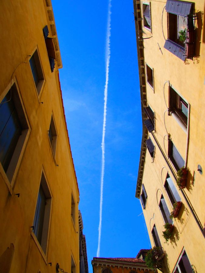 Leaving Venice – Looking Up. The vapour trail seems to almost tear the photo in half. The sun was just out of sight over the roofs to my left, still illuminating the upper part of the building to my right. The composition was all there so I took the shot. https://witness.theguardian.com/assignment/556c31aee4b0ce954cb1887a/1576711