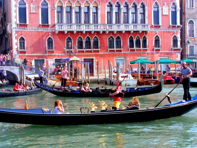 A Snapshot Of Bagpipes In Venice. A rare sight captures everyone's attention as the gondola with the brightly dressed bagpipe player passes the Palazzo Bembo, Riva del Carbon, 4793-4785, 30124 Venezia, built by the noble Bembo family in the 15th century. The building is now one of the European Cultural Centre's contemporary art exhibition venues in Venice as well as housing a hotel on the top floor. https://witness.theguardian.com/assignment/559d15cce4b032a39a3bb39a/1651283